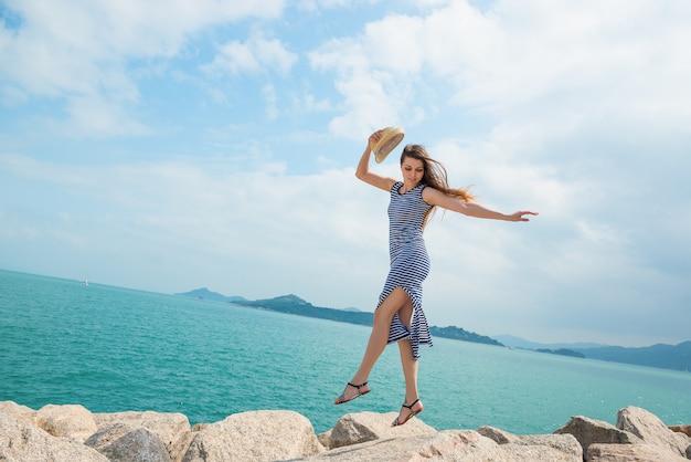 Aantrekkelijk meisje in jurk springt op rotsen op het strand. actieve vrijetijdsbesteding, gezondheid, toerisme, vakantiethema. Premium Foto