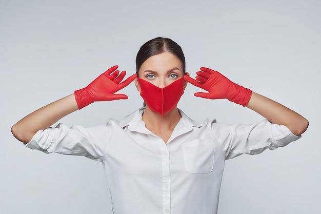 Aantrekkelijk meisje in rode handschoenen en een gezichtsmasker. Premium Foto