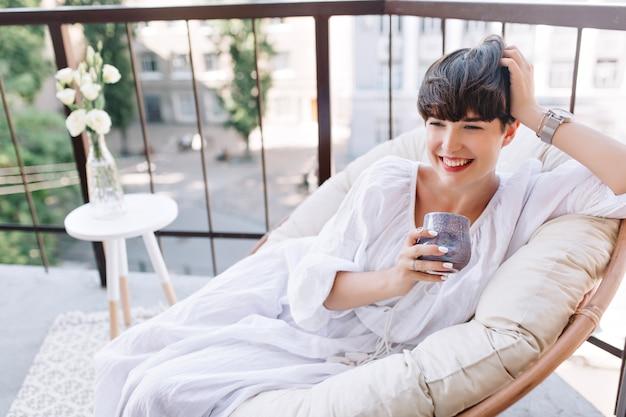 Aantrekkelijk meisje in witte zomerjurk liggend op de bank op terras met kopje koffie en lachen Gratis Foto