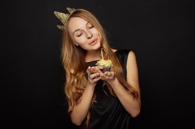Aantrekkelijk meisje met een kroon en cupcake Gratis Foto