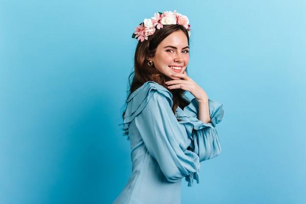 Aantrekkelijk meisje met een ondeugende glimlach kijkt naar de camera. foto van dame in blauwe jurk met kroon van bloemen. Gratis Foto