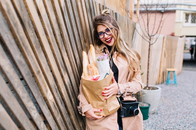 Aantrekkelijk meisje met lang haar tevreden met winkelen leunde tegen het houten hek. stijlvolle jonge vrouw in bruine kleding poseren met tas uit de supermarkt en lachen op de straat achtergrond. Gratis Foto