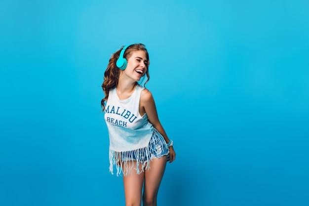 Aantrekkelijk meisje met lang krullend haar in de staart heeft plezier op blauwe achtergrond in de studio. ze draagt een wit t-shirt, een korte broek en luistert naar energieke muziek met een blauwe koptelefoon. Gratis Foto