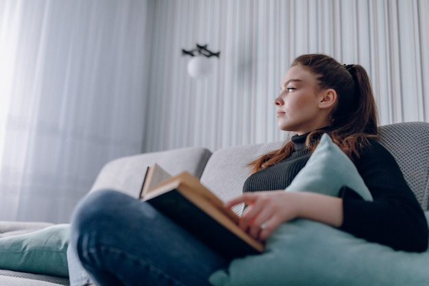 Aantrekkelijk meisje op de bank leest een papieren boek. geestelijke ontwikkeling. nuttig gebruik van tijd thuis. comfort voor thuis. Gratis Foto