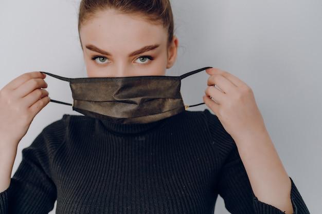 Aantrekkelijk meisje op een lichte muur draagt een medisch masker. gebruik van persoonlijke bescherming. anti-epidemie en bescherming tegen vervuiling van de persoon. Gratis Foto