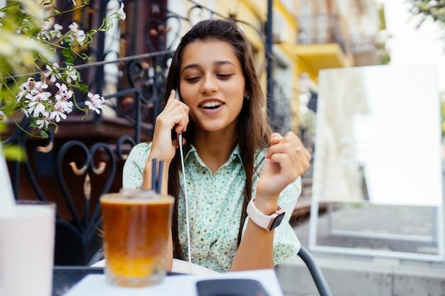 Aantrekkelijk meisje zit straat café terras, praten smartphone, bel vriend Gratis Foto