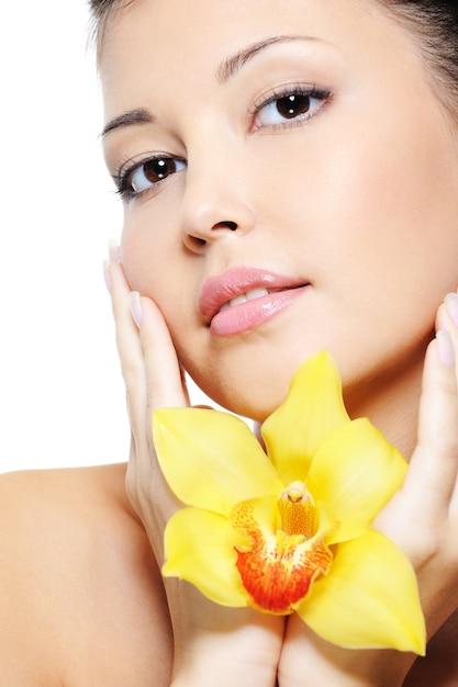 Aantrekkelijk sensualiteit aziatisch vrouwelijk gezicht met bloem op handen Gratis Foto