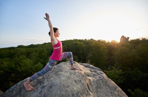 Aantrekkelijk slank meisje dat uitrekkende yogaoefeningen bovenop reusachtige rots doet Premium Foto