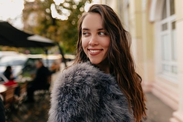 Aantrekkelijk stijlvol kaukasisch meisje in bontjas wegkijken en glimlachend op stad Gratis Foto