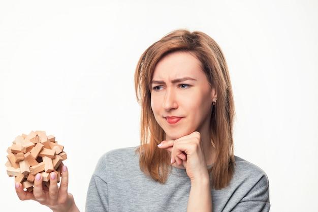 Aantrekkelijke 24-jarige zakenvrouw op zoek verward met houten puzzel. Gratis Foto