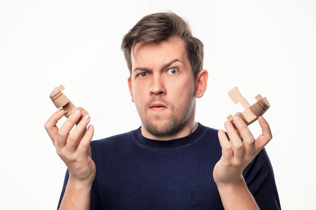 Aantrekkelijke 25-jarige zakenman op zoek verward met houten puzzel. Gratis Foto