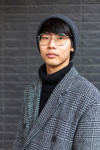 Aantrekkelijke aziatische jonge man met jas, hoed en bril. street fashion concept Premium Foto