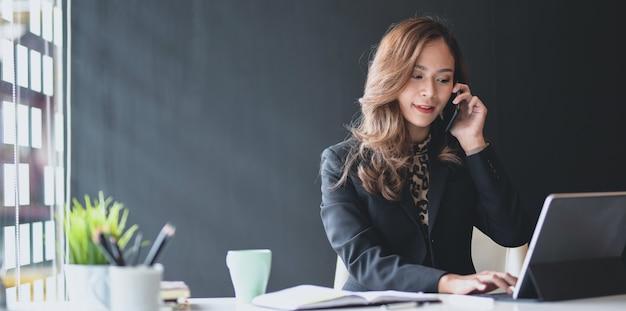 Aantrekkelijke aziatische onderneemster die op de telefoon met klant spreekt Premium Foto