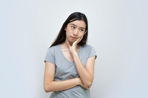 Aantrekkelijke aziatische vrouw die geïsoleerd, mooi aziatisch jong meisje denkt Premium Foto