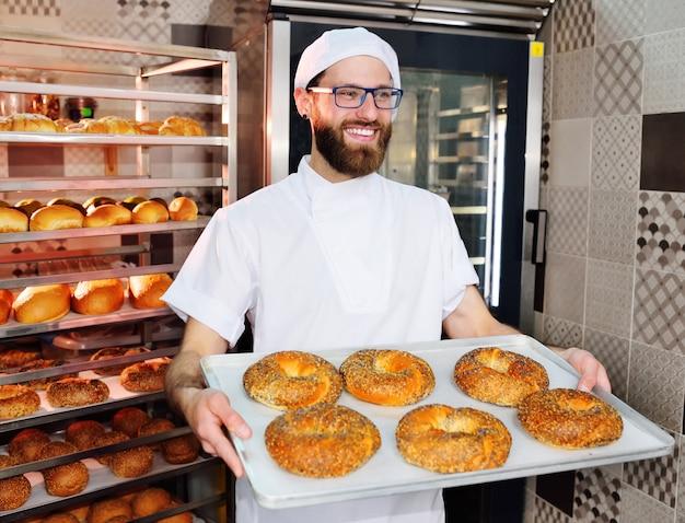Aantrekkelijke baker in witte uniform met een dienblad met vers gebakken bagels met sesam en maanzaad Premium Foto
