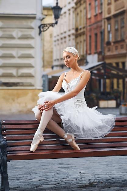 Aantrekkelijke ballerina zittend op de bank in de stad Gratis Foto