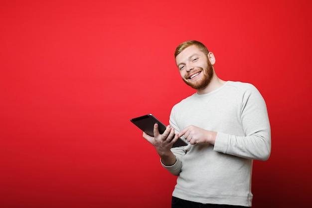 Aantrekkelijke bebaarde man glimlachend en camera kijken terwijl staande op heldere rode achtergrond en met behulp van moderne tablet Premium Foto