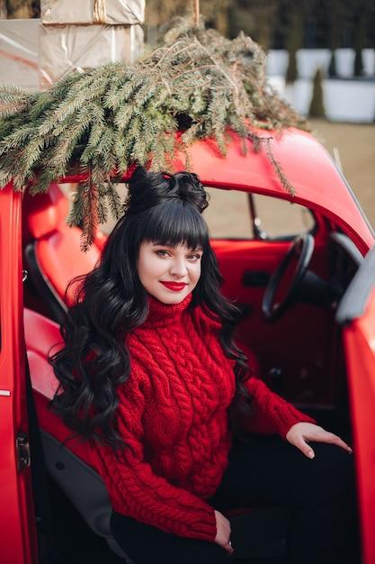 Aantrekkelijke blanke vrouw zit in de bestuurdersstoel van de auto en glimlacht Gratis Foto