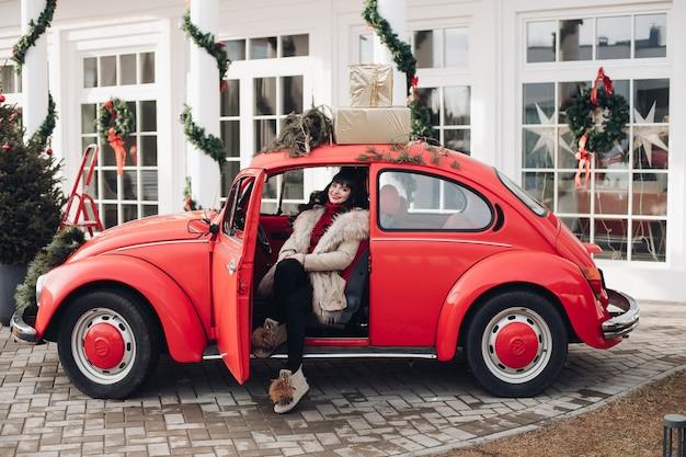 Aantrekkelijke blanke vrouw zit in de bestuurdersstoel van de auto Gratis Foto