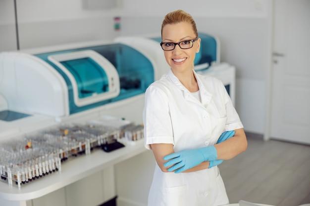 Aantrekkelijke blonde glimlachende laboratoriumassistent die zich in laboratorium met gekruiste handen bevindt. Premium Foto