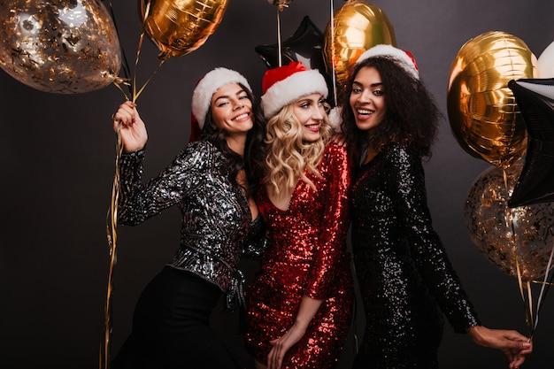 Aantrekkelijke blonde vrouw in rode jurk wintervakantie vieren met vrienden Gratis Foto