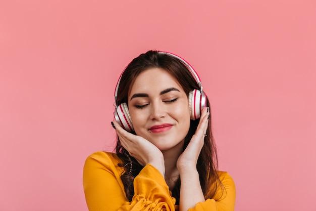 Aantrekkelijke brunette met glimlach en gesloten ogen luisteren naar lied in koptelefoon. dame in felgele blouse poseren op geïsoleerde muur. Gratis Foto