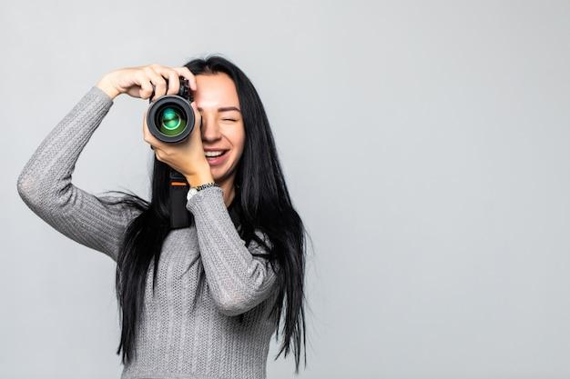 Aantrekkelijke brunette richt haar camera. het samenstellen van een foto in de studio, geïsoleerd op grijze muur Gratis Foto