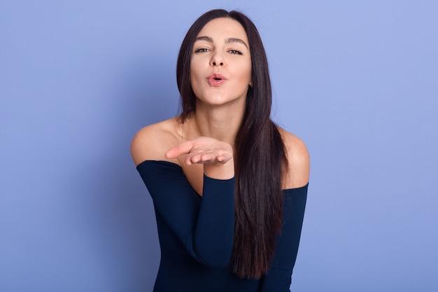 Aantrekkelijke brunette vrouw blaast kus op camera op blauw, jong vrouwelijk model draagt elegante jurk poseren met blote schouders, aantrekkelijk meisje met perfecte huid en lang staraight haar Gratis Foto