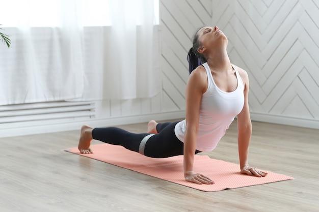 Aantrekkelijke brunette vrouw doet yoga thuis. Gratis Foto