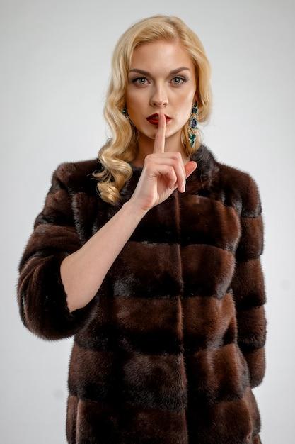 Aantrekkelijke dame in bruine bontjas. perfecte make-up, rode mat lippen en blauwe ogen. Premium Foto