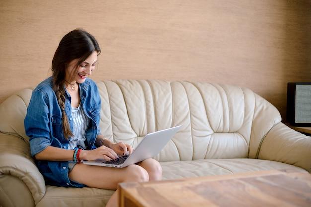 Aantrekkelijke dame usig laptop op leerbank Gratis Foto