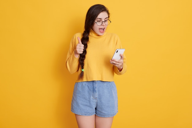 Aantrekkelijke donkerbruine vrouw die gelukkig iets schreeuwt terwijl het bekijken slimme telefoon in haar handen Gratis Foto