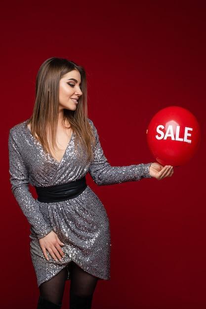 Aantrekkelijke donkerbruine vrouw in cocktailkleding met rode luchtballon Premium Foto
