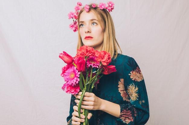 Aantrekkelijke dromerige sensuele vrouw met kroon op hoofd en boeket bloemen Gratis Foto