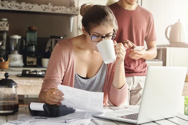 Aantrekkelijke ernstige vrouw in bril koffie drinken en document in haar handen bestuderen, gezinsbudget beheren en papierwerk doen aan keukentafel met stapel rekeningen, laptop en rekenmachine Gratis Foto