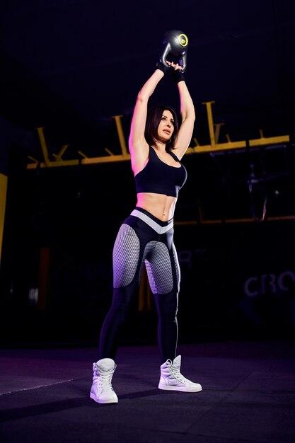 Aantrekkelijke fit middelbare leeftijd vrouw atleet uitvoeren van een waterkoker bell swing in cross fit gym Premium Foto