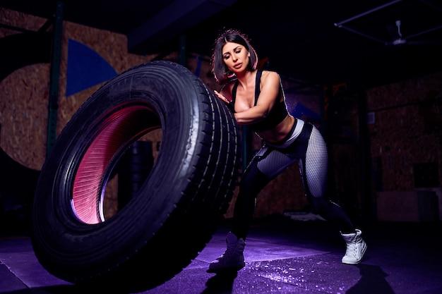 Aantrekkelijke fit middelbare leeftijd vrouwelijke atleet trainen met een enorme band, draaien en flippen in de sportschool. cross fit vrouw te oefenen met grote band Premium Foto
