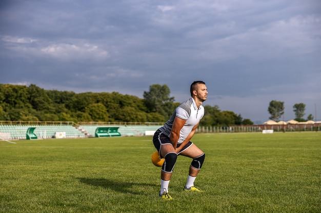 Aantrekkelijke fitte voetballer die op het veld staat en zwaaiende ketelbel. Premium Foto