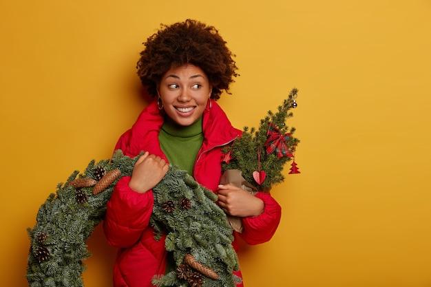 Aantrekkelijke gekrulde vrouw glimlacht toothily, kijkt opzij, gekleed in bovenkleding, houdt kleine ingerichte firtree en sparren krans Gratis Foto