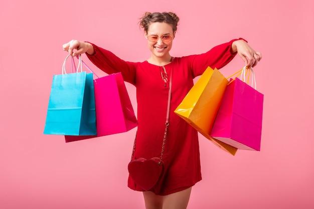 Aantrekkelijke gelukkig lachende stijlvolle vrouw shopaholic in rode trendy jurk met kleurrijke boodschappentassen op roze muur geïsoleerd, verkoop opgewonden, modetrend Gratis Foto