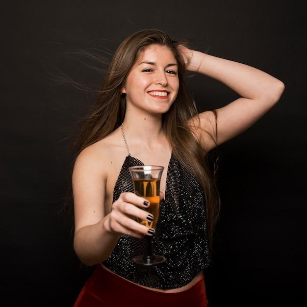 Aantrekkelijke gelukkige dame in avonddoek met een glas drank en hand op het hoofd Gratis Foto