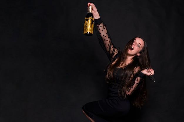 Aantrekkelijke gelukkige dame in avondjurk met een fles drank Gratis Foto