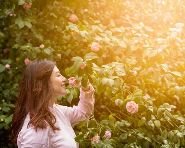 Aantrekkelijke gelukkige vrouw die het roze bloem groeien op groen takje houdt Gratis Foto