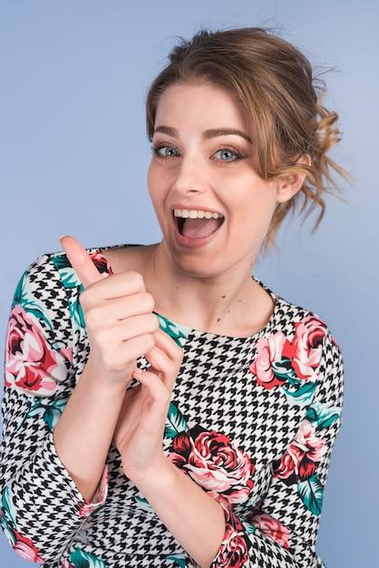 Aantrekkelijke gelukkige vrouw in jurk met duim omhoog Gratis Foto