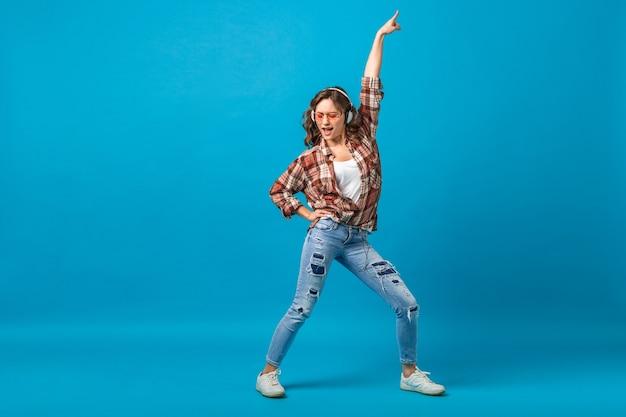 Aantrekkelijke gelukkige vrouw poseren in vrolijke bui luisteren naar muziek in koptelefoon in geruit overhemd en spijkerbroek geïsoleerd op blauwe studio achtergrond, opzoeken Gratis Foto