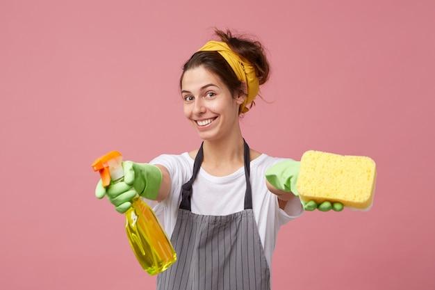 Aantrekkelijke glimlachende jonge vrouw gekleed in vrijetijdskleding en beschermende kleding die haar armen uitstrekt met schoonmaakspray en spons alsof ze zegt: wil je me helpen met huishoudelijk werk? Gratis Foto
