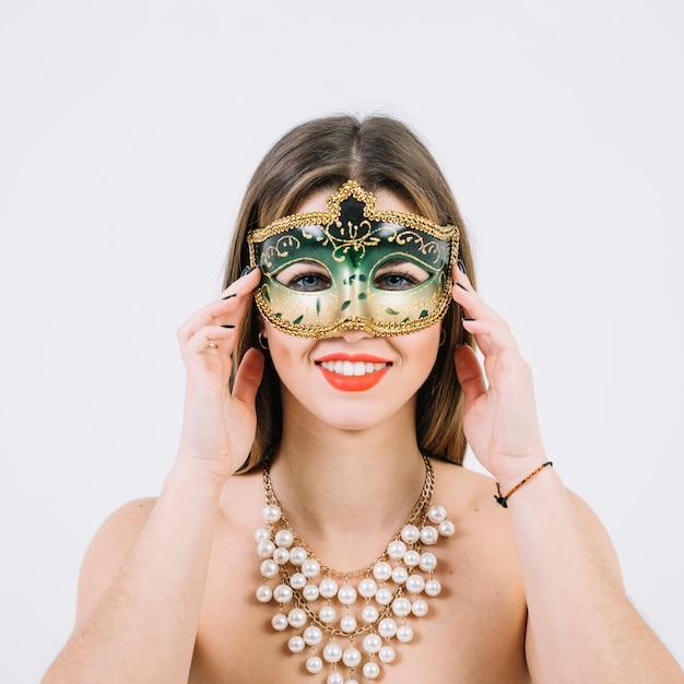Aantrekkelijke glimlachende vrouw in maskerade carnaval masker op witte achtergrond Gratis Foto