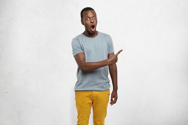 Aantrekkelijke grappige geschokte jonge donkere man gekleed terloops wijzend zijn wijsvinger zijwaarts op grijze blinde muur, met iets verbazingwekkends erop. menselijke gezichtsuitdrukkingen en emoties Gratis Foto