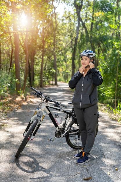 Aantrekkelijke hogere aziatische vrouw met fiets in park Premium Foto