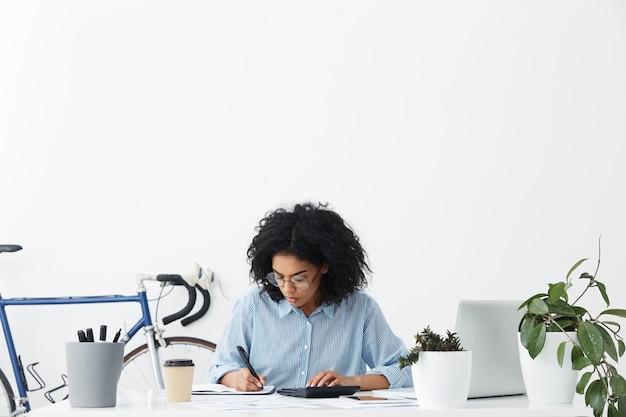 Aantrekkelijke jonge afrikaanse amerikaanse vrouwelijke accountant die blauw overhemd en oogglazen draagt Gratis Foto